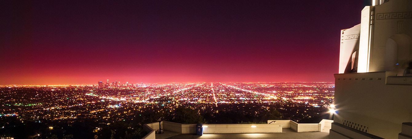 A photo of city lights across Los Angeles, taken at night looking southward from Griffith Observatory. Downtown Los Angeles is visible on the left.