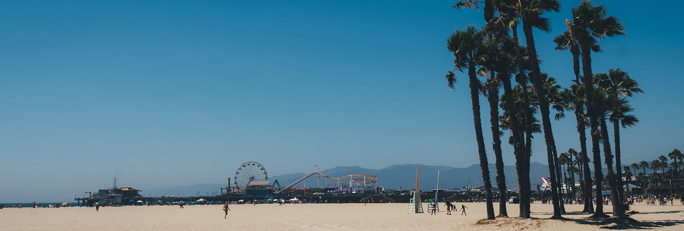 A photo of a beautiful day at Santa Monica beach showing sand, palm trees and beachgoers. The Santa Monica Pier and Santa Monica mountains can be seen in the background of the photo against a blue, cloudless sky.