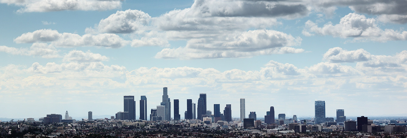 A photo showing the Downtown Los Angeles skyline against a blue sky dotted with clouds.
