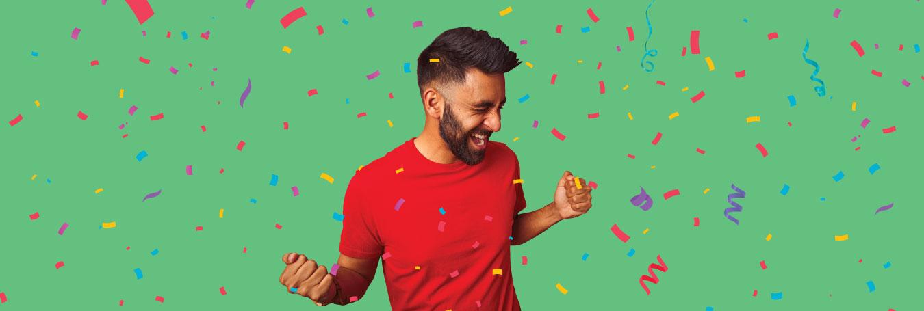 Hispanic male clenches his fists in celebration has confetti falls around him